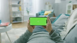 Man at Home Lying on a Couch using Smartphone, Holds it Horizontally in Landscape Mode. Playing Video Games, Watching Videos. Screen Has Tracking Markers. Point of View Camera Shot.