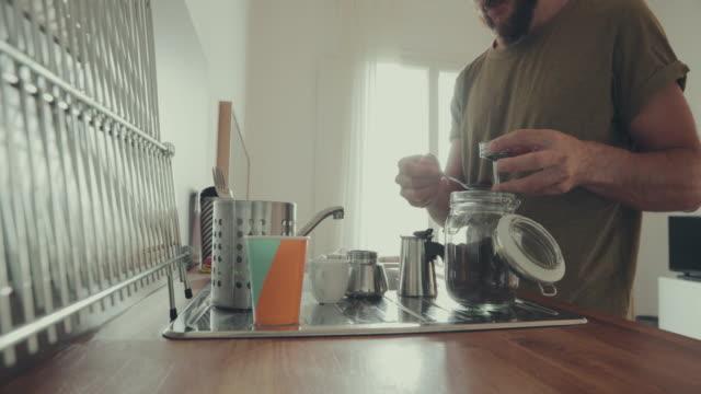 man at home, preparing coffee in moka - bricco per il caffè video stock e b–roll