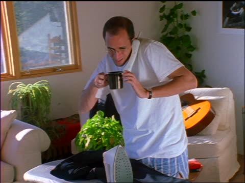 man at home talking on phone by ironing board / he drinks coffee + burns mouth - sladdlös telefon bildbanksvideor och videomaterial från bakom kulisserna