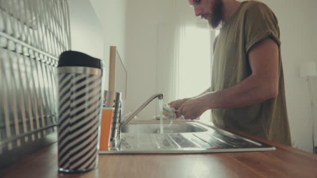 vídeos y material grabado en eventos de stock de hombre en la casa, lavar los platos - hípster urbano