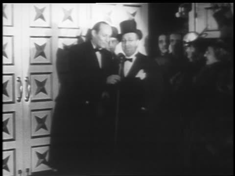 b/w 1935 man at microphone introducing ed wynn at jumbo opening / hippodrome theater baltimore - 1935年点の映像素材/bロール