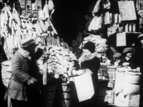 b/w 1930 man at outdoor salami stand talking to woman shopping / new york city / newsreel - anno 1930 video stock e b–roll