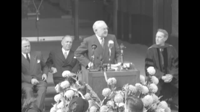 Man at podium in front of audience gathered outdoors in front of new building introduces Mayor of Los Angeles Fletcher Bowron Bowron seated with...
