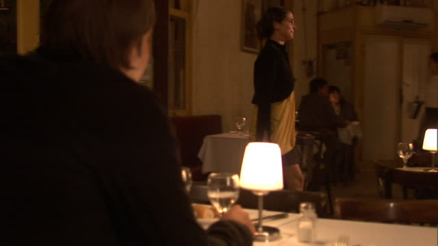 MS SLO MO ZI Man at restaurant table starting at woman as she walks in/ Woman walking over to bar and turning to stare at man/ Buenos Aires, Argentina