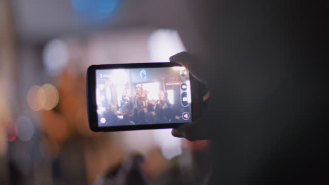 stockvideo's en b-roll-footage met man at rock concert taps smartphone touchscreen to focus image on band - draadloze technologie