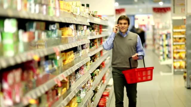 Uomo al supermercato con cellulare