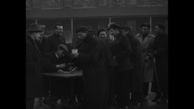 ms man at table signs pieces of paper and then hands them to members of the auxiliary division of the royal irish constabulary as they pass by table... - sinn fein stock videos & royalty-free footage