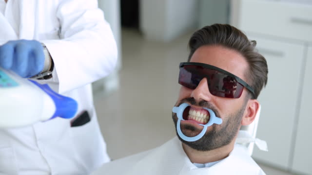 stockvideo's en b-roll-footage met man bij teeth bleken - beschermend masker werkkleding