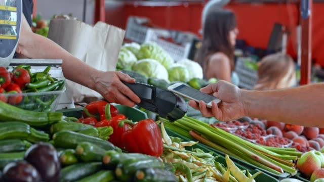 man at the marketplace paying for produce with his mobile phone - paying stock videos & royalty-free footage