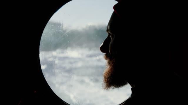vidéos et rushes de homme à la fenêtre de hublot d'un bateau naviguant la mer agitée - hublot