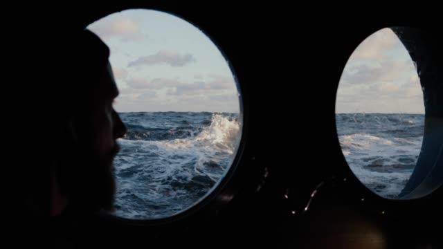 man på hytt ventil fönster av en båt segling grov havet - profil redigerat segment bildbanksvideor och videomaterial från bakom kulisserna