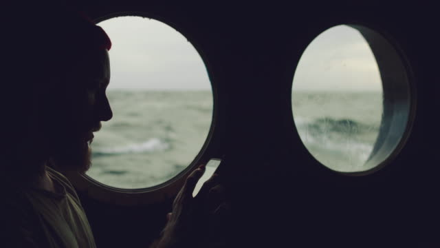man at the porthole window of a vessel in a rough sea - imbarcazione per passeggeri video stock e b–roll