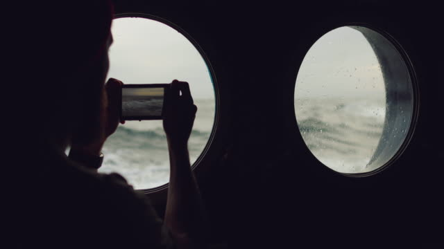 man at the porthole window of a vessel in a rough sea - marinaio video stock e b–roll