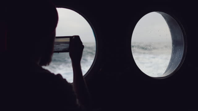 Man at the porthole window of a vessel in a rough sea