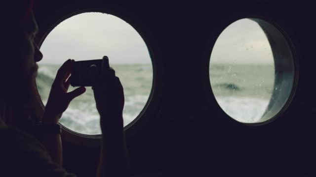 vídeos de stock, filmes e b-roll de homem à janela vigia de um navio em um mar agitado - marinheiro