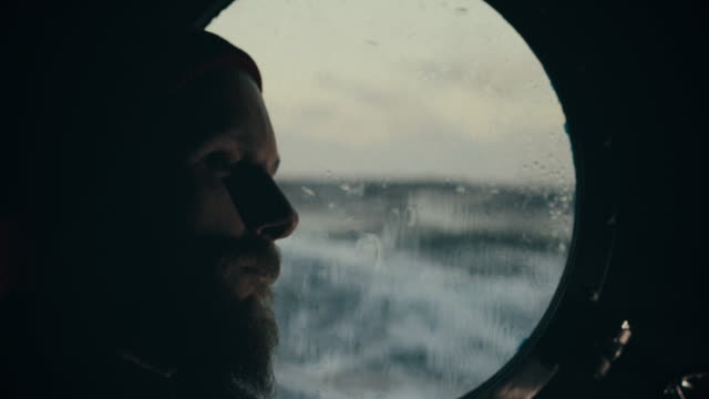 man at the porthole window of a vessel sailing the sea: alone and homesick - travel destinations stock videos & royalty-free footage