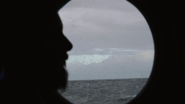 man at the porthole window of a vessel sailing the sea - sailor stock videos & royalty-free footage
