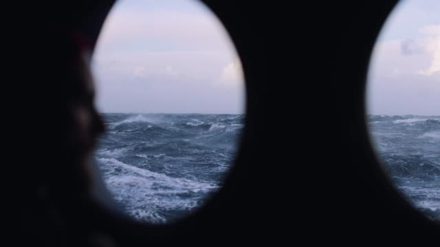 mann am portholzfenster eines seeschiffs - passagier wasserfahrzeug stock-videos und b-roll-filmmaterial