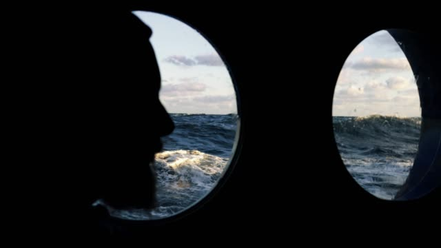 vídeos de stock e filmes b-roll de man at the porthole window of a vessel sailing the sea - marinheiro