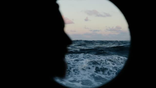 vidéos et rushes de homme à la fenêtre de hublot d'un navire naviguant la mer - hublot