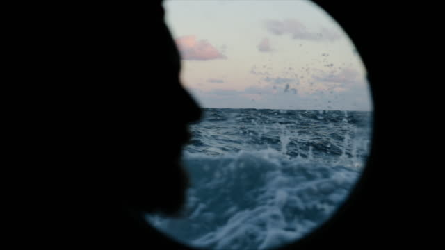 vídeos de stock e filmes b-roll de man at the porthole window of a vessel sailing the sea - perfil