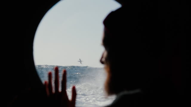 man at the porthole window of a vessel sailing the sea - fishing boat stock videos & royalty-free footage
