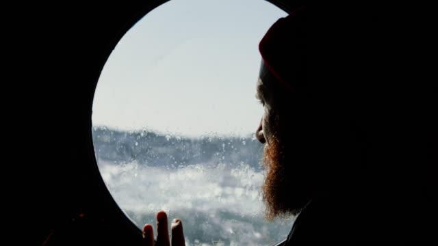 stockvideo's en b-roll-footage met man op het patrijspoort venster van een schip dat de zee zekt - vissersboot