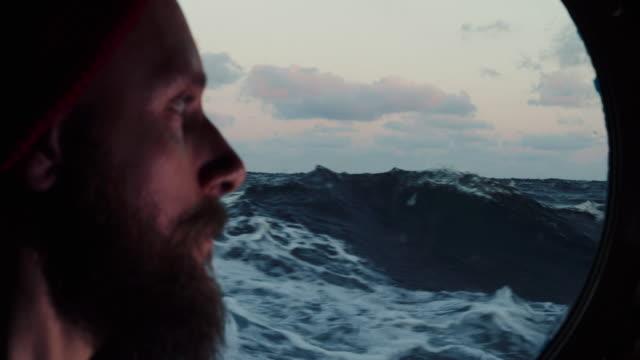 vidéos et rushes de homme à la fenêtre de hublot d'un bateau naviguant la mer - marin