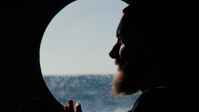 man at the porthole window of a vessel sailing the sea - sailing ship stock videos & royalty-free footage
