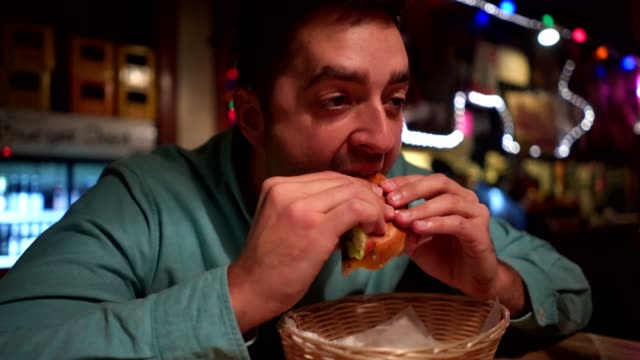 mann in der kneipe einen burger essen - schnellimbiss stock-videos und b-roll-filmmaterial