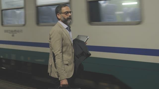 man at train station - arrivo video stock e b–roll