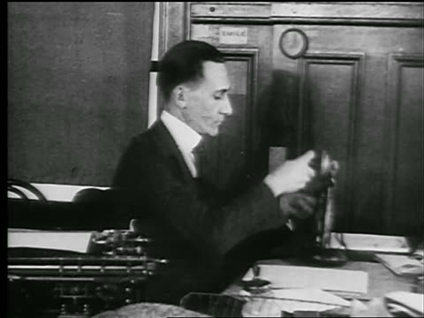b/w 1927 man at typewriter answers telephone + starts writing on paper (newspaper reporter?) - 1920 stock-videos und b-roll-filmmaterial