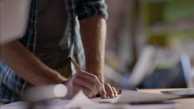 stockvideo's en b-roll-footage met man at workbench takes notes on graph paper - innovatie