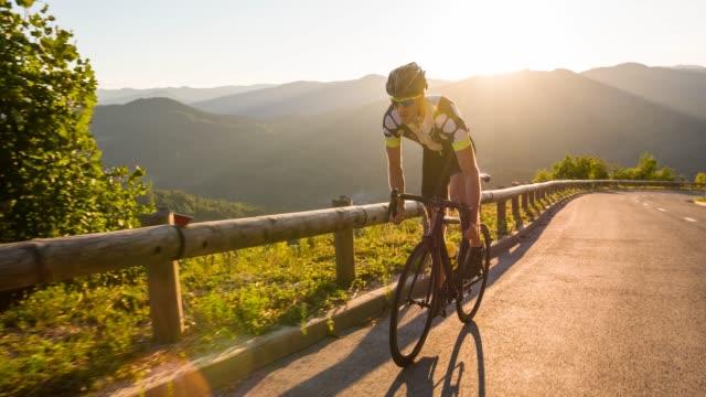 vidéos et rushes de athlète d'homme se tenant debout tandis que le cyclisme de route en montée, entraînement de sport au coucher du soleil - qui monte