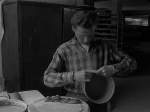a man attaches handles to a clay bowl at the stavanger pottery workshop 1959 - 付着点の映像素材/bロール