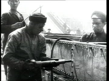 1914 b/w ms pan man attaching bolts with soldering device in industrial yard/ russia - steel stock videos & royalty-free footage