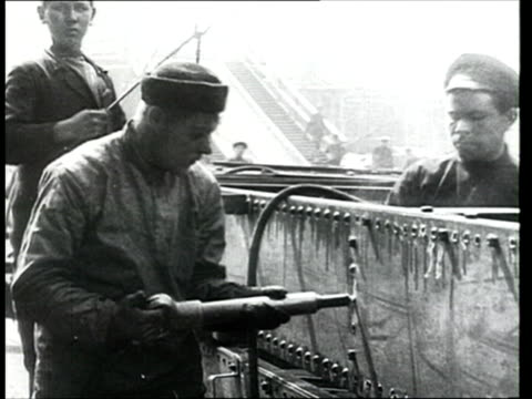vidéos et rushes de 1914 b/w ms pan man attaching bolts with soldering device in industrial yard/ russia - ouvrier