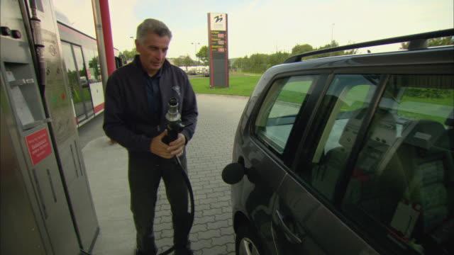 vídeos y material grabado en eventos de stock de ms man attaching nozzle of natural gas fueling pump to gas tank of passenger car / marburg, germany - bomba de combustible