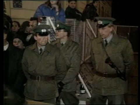 stockvideo's en b-roll-footage met 91189 bv man attacking berlin wall with axe ms east german police officers standing watching ms east germans in trabant car towards past cheering... - bijl