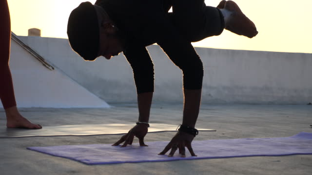 ms man attempting fingertip handstand after rooftop yoga class - tights stock videos & royalty-free footage