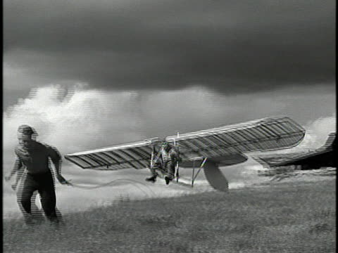 1940 B/W WS PAN Man attempting to fly on homemade hang glider / USA