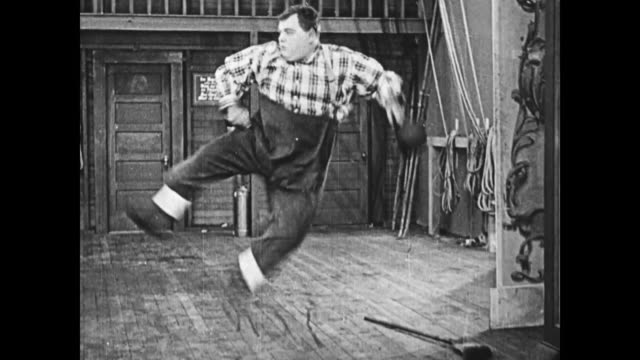 1919 man (fatty arbuckle) attempts a vaudeville dance routine and loses his balance while kicking his legs high in the air, he falls to the floor and uses a broomstick to uncross his stuck legs. - careless stock videos & royalty-free footage