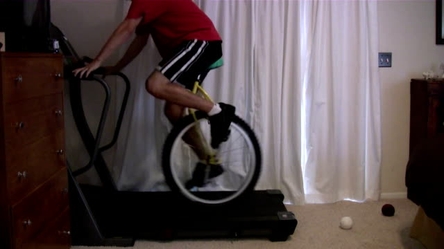 vidéos et rushes de / man attempts stunt riding a unicycle on a moving treadmill / man falls off unicycle and then the treadmill send him flying to the ground man falls... - exploit sportif