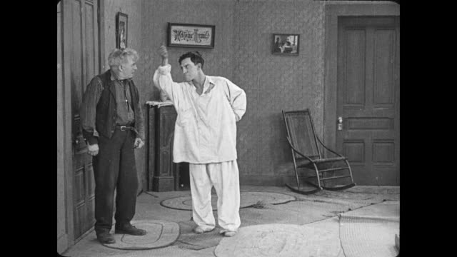 vidéos et rushes de 1922 man (buster keaton) attempts to fight an old man but is instead kicked in the face by the old man and knocked unconscious - donner un coup de pied