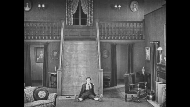 1921 man (buster keaton) attempts to outwit disappearing staircase - 1921 stock-videos und b-roll-filmmaterial