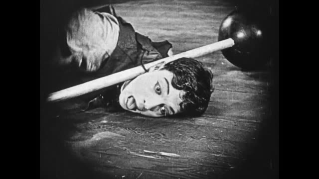1919 Man (Fatty Arbuckle) attempts to release man's (Buster Keaton) head from underneath the barbells, and the weights are too heavy for him to lift, but the strongman's assistant (Molly Malone) easily lifts the barbells and frees Keaton