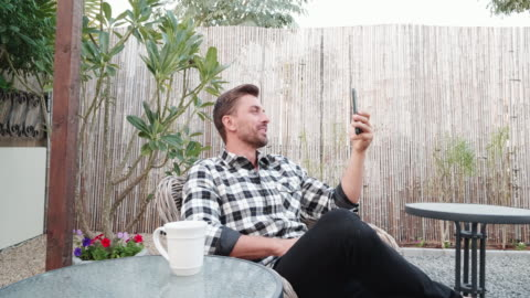 man attending to video call using a smartphone - hot drink stock videos & royalty-free footage