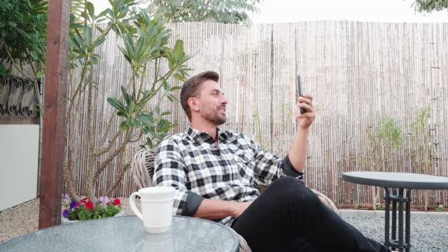 vídeos de stock e filmes b-roll de man attending to video call using a smartphone - bebida quente