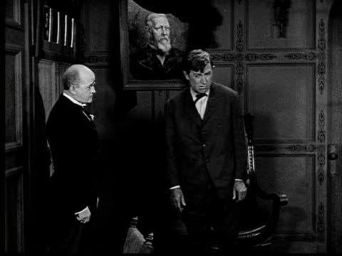 vidéos et rushes de 1924 b&w ms man awkwardly looking around room and at portrait as butler watches  - calvitie