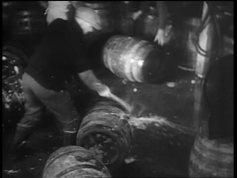 b/w 1932 man axing barrels of beer / beer spraying out of barrels / chicago - anno 1932 video stock e b–roll